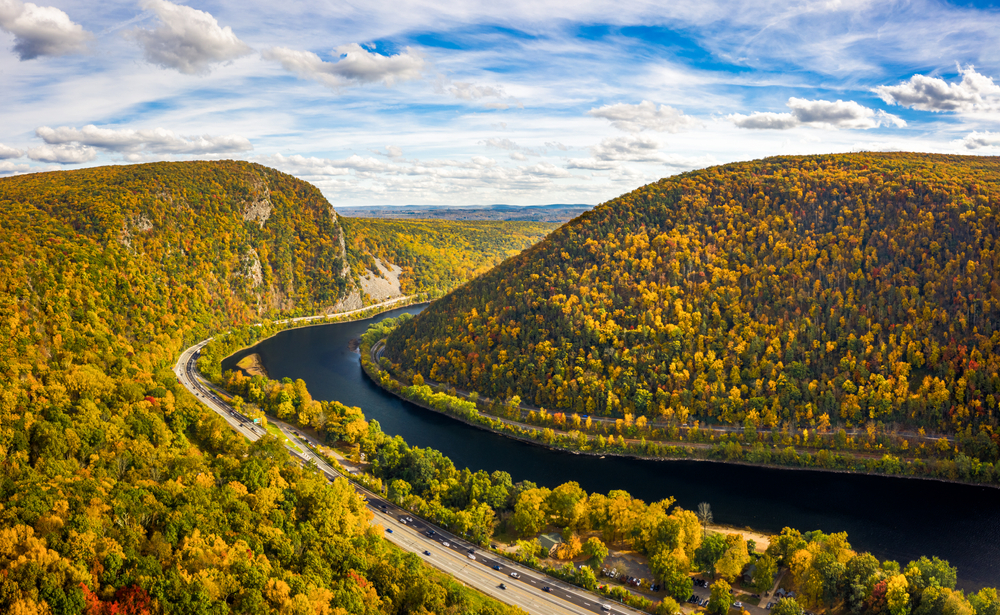 Cars drive on a road that parallels a river, winding between mountain ridges.