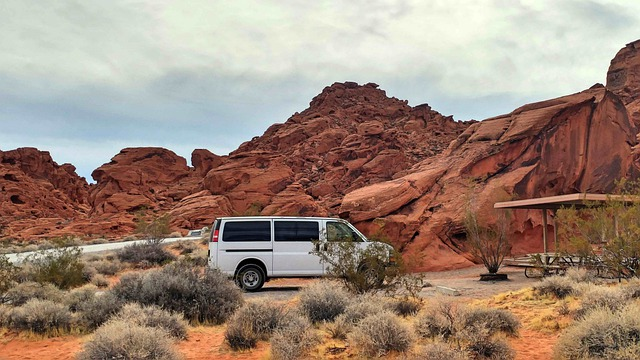 a van camped by some red rocks