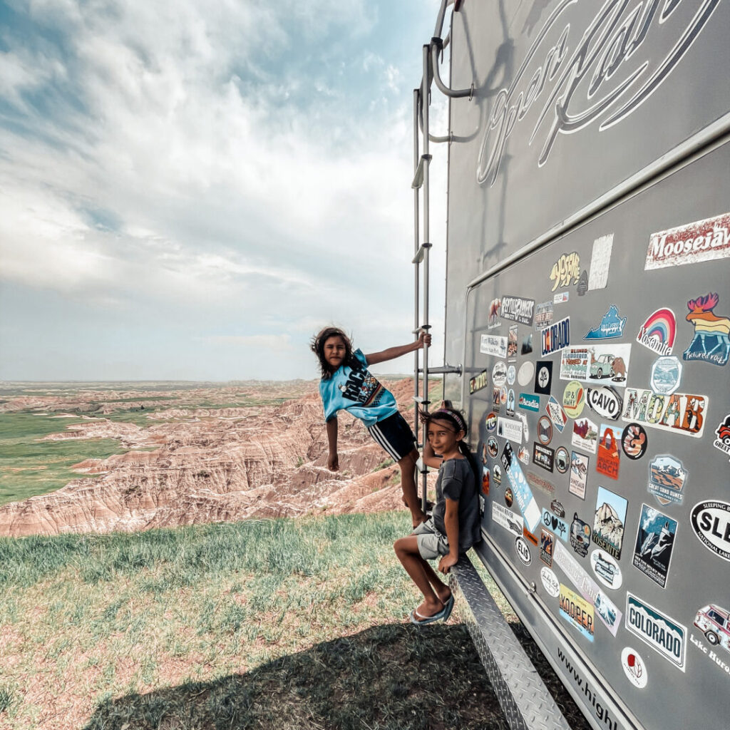 Child hangs off back ladder of an RV in Badlands NP