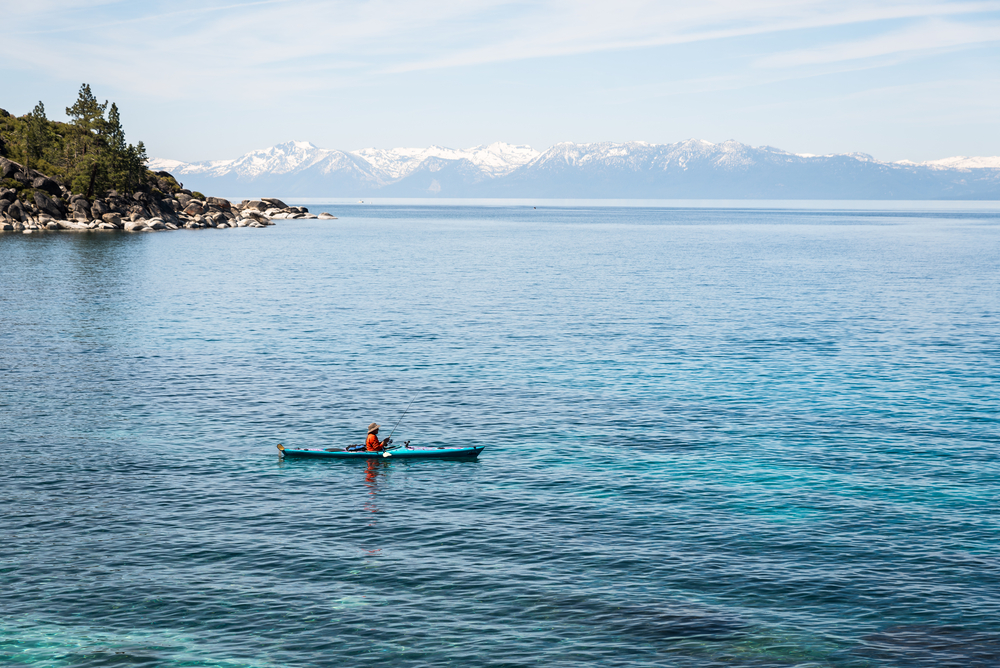 A person in fishing from a kayak on a large blue lake.