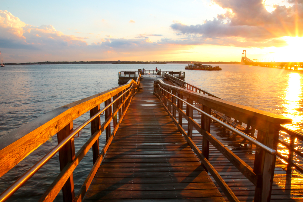 The sun rises and turns the water by a wooden pier golden. Several people stand, fishing, at the edge of the pier.