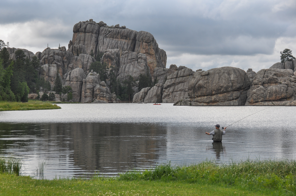 A man stands in the middle of a lake, casting a fishing pole toward deeper waters. Rocky cliffs make up the other bank.