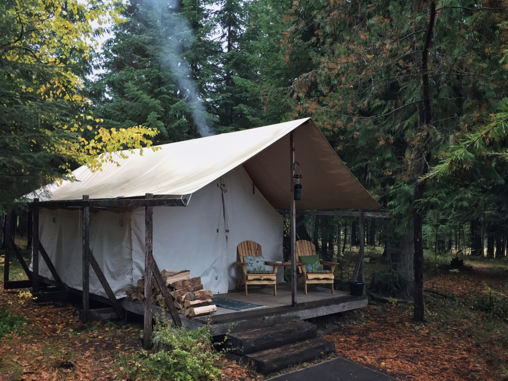 A luxury tent sits in the middle of a forest. There are two chairs and a woodpile on its porch, and smoke rises from the back.