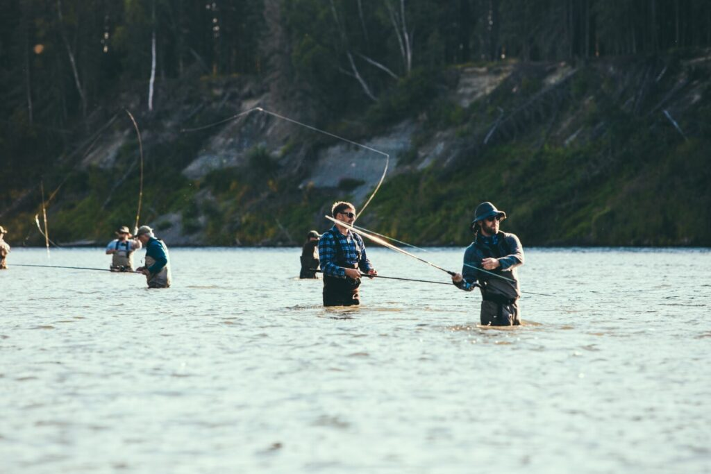 A group of men wading in a river and fly-fishing.