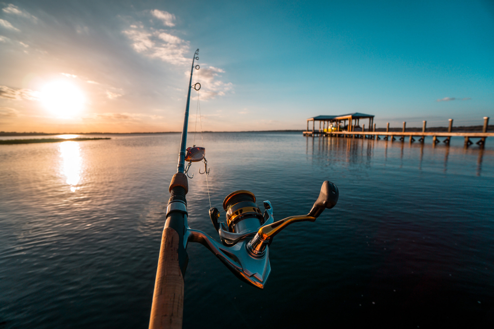 A cast fishing pole in a calm body of water, next to a long wooden dock. The sun sets over the horizon