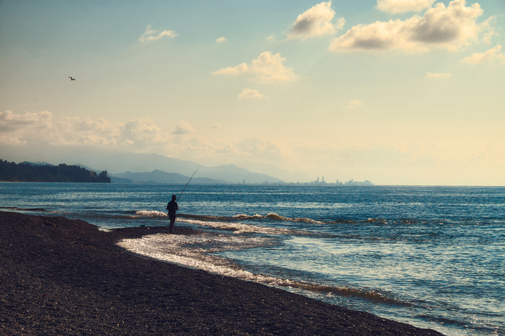 A person fishing on a beach while the waves rush toward the shore.