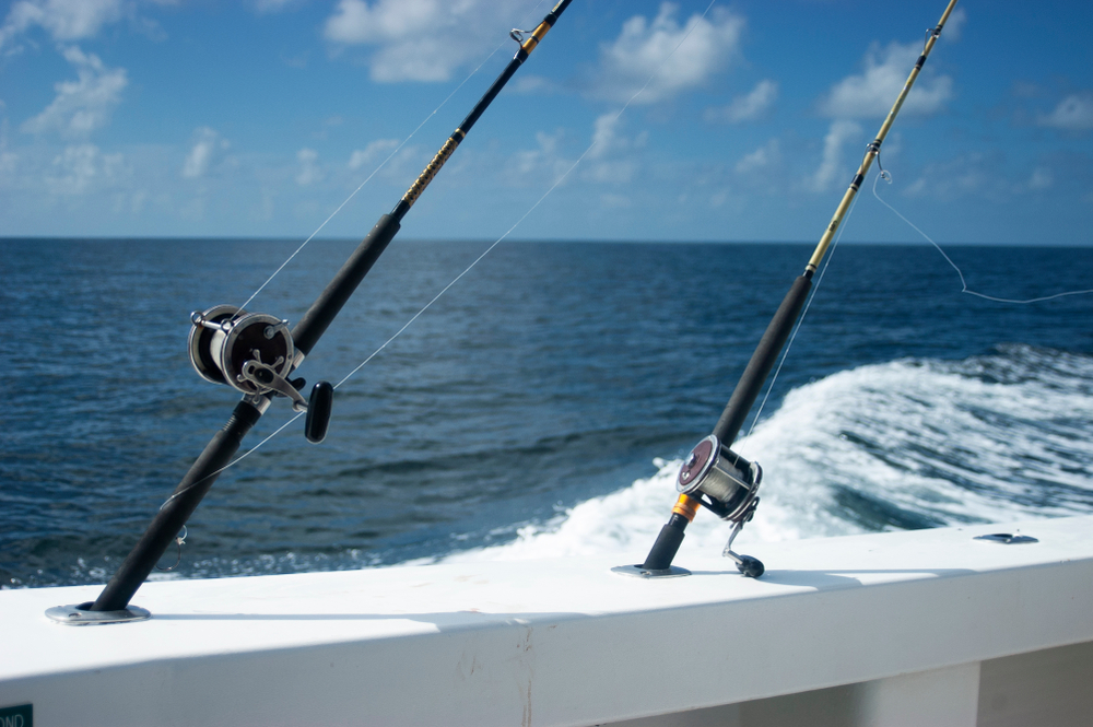 Two fishing rods slotted into holes in the railing on a deep-sea fishing vessel.