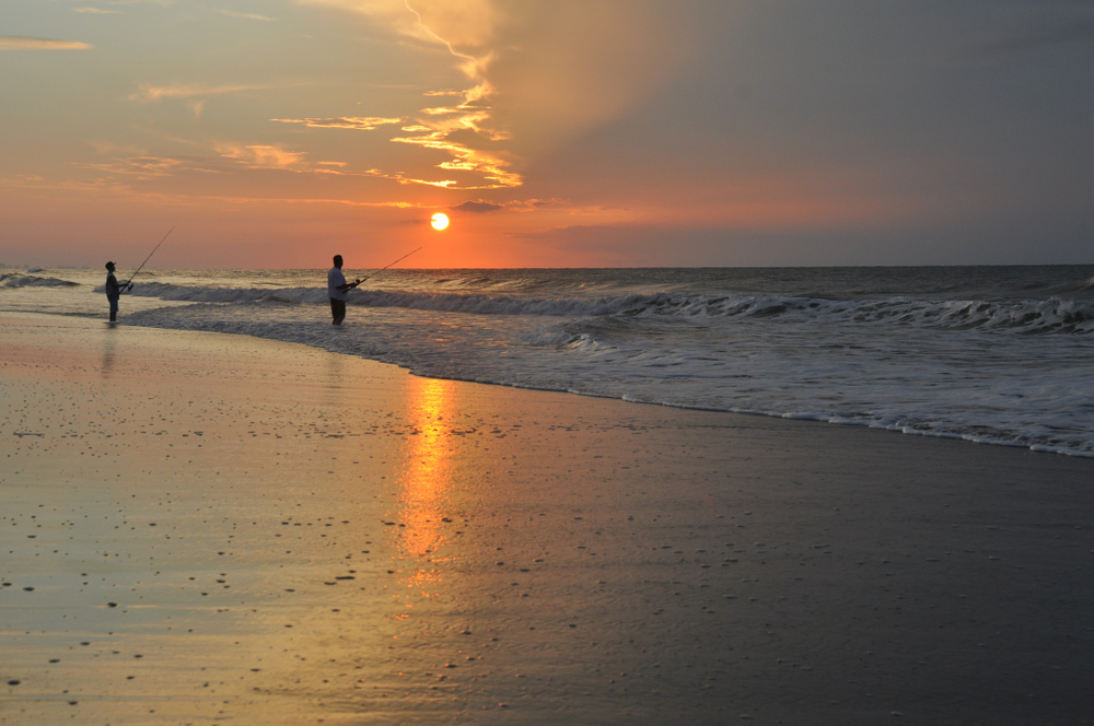 Silhouette of a man and a boy fishing in the ocean against an orange, yellow, and grey sunrise.