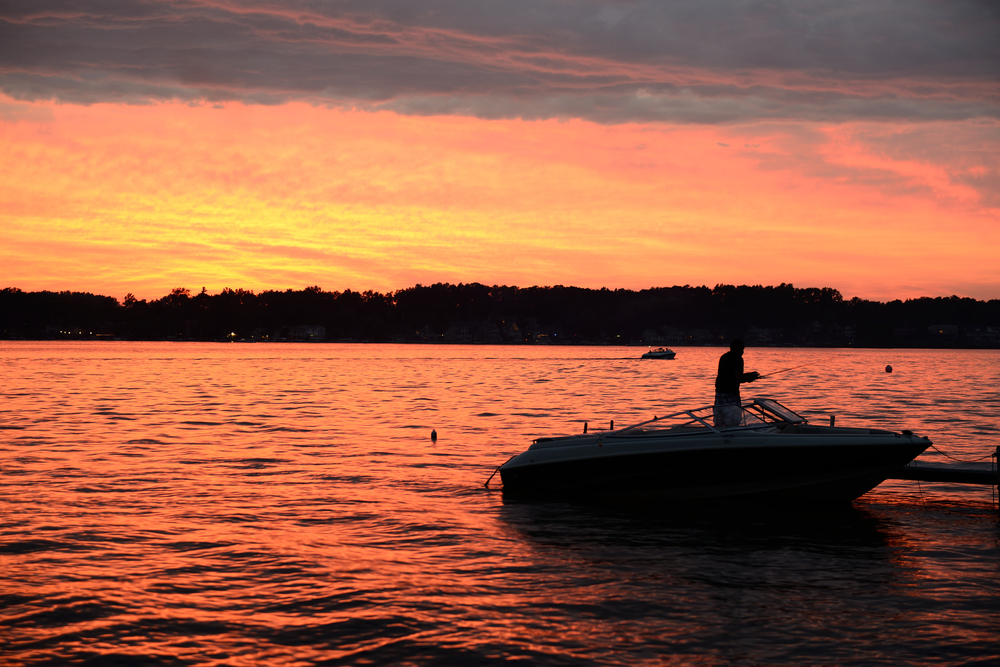 A man in a boat casting a fishing pole, silhouetted by the setting sun.