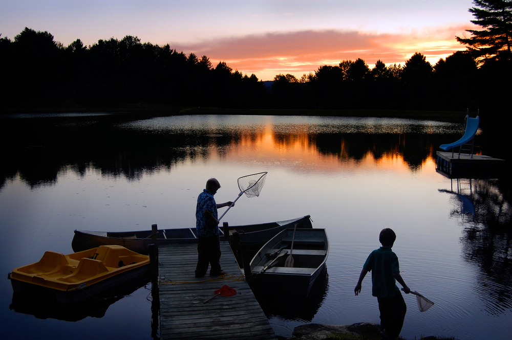 A man and a child standing with nets at a short dock, where a paddle boat and a row boat are docked. The sun rises over trees on the other bank.