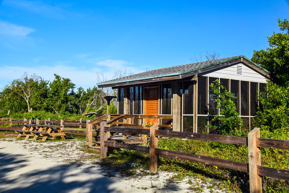 A beachside screened-in campsite with a low wooden fence, surrounded by green vegetation.