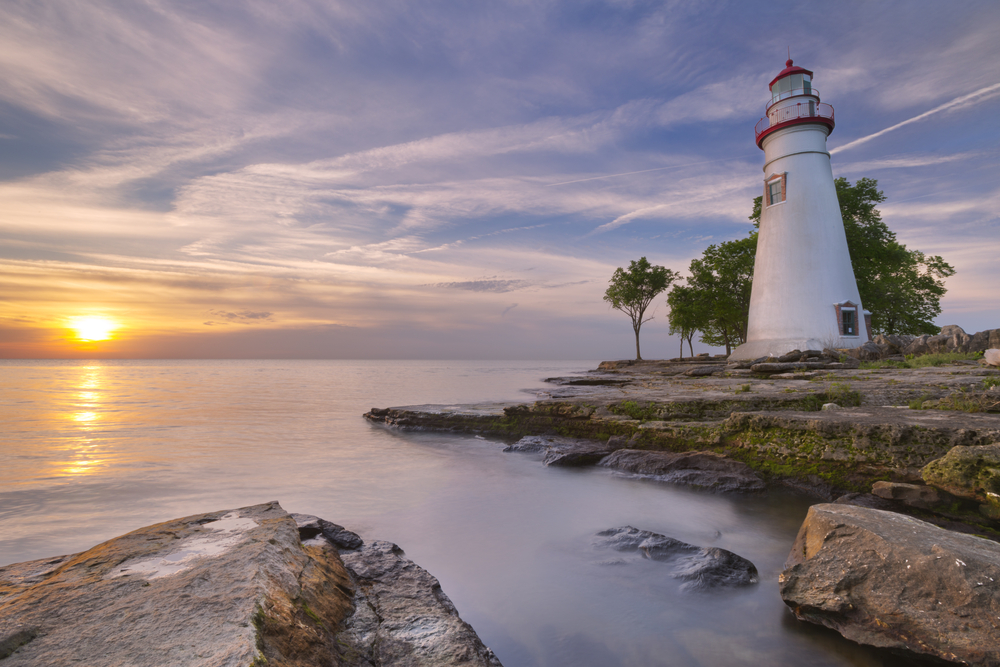 A white lighthouse sits on the shore of a lake as the sun sets in the distance.