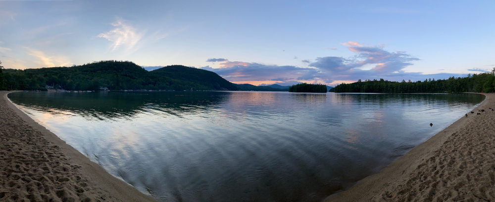 Bristol, New Hampshire (NH) / USA - August 21, 2020: Wellington State Park swimming lake beach panoramic at sunset with ducks on edge of Follansbee cove with sugarloaf mountain in background.  J