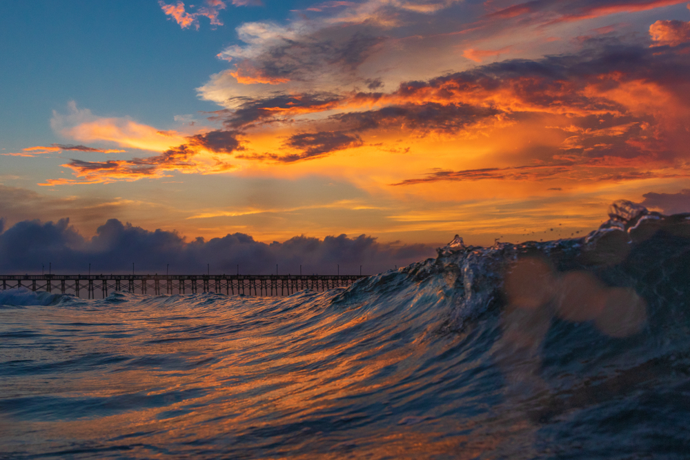 Sunrise or sunset with gorgeous orange sky and a pier in the distance.