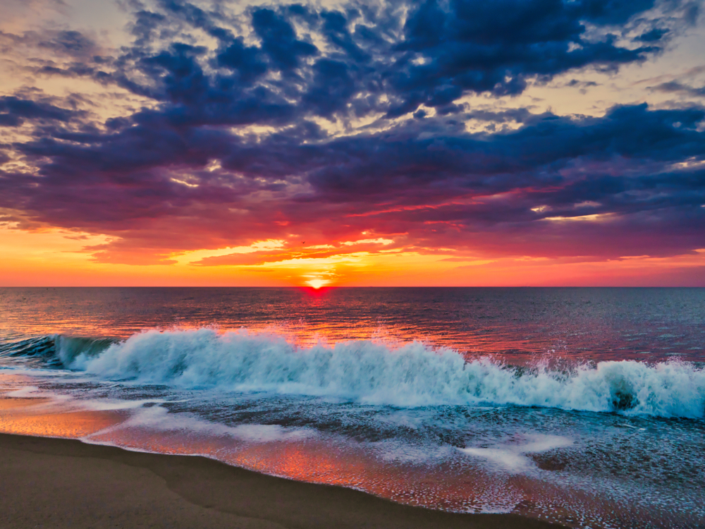 The sun rises over the ocean. Waves crash into the sandy shore.