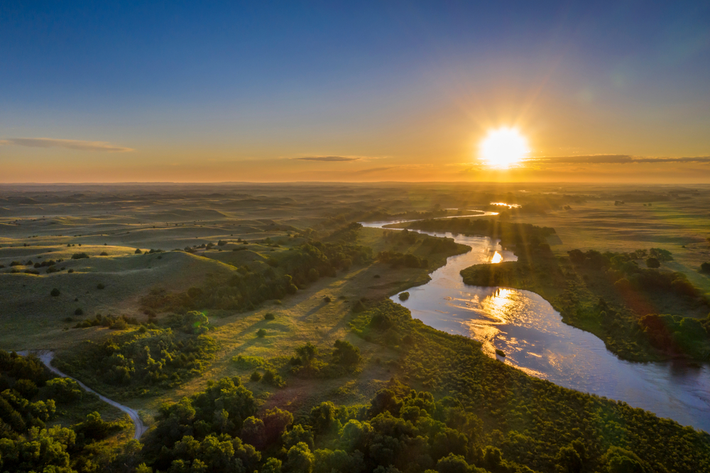 The sun rises over grassy hills with trees. A river meanders across the landscape.