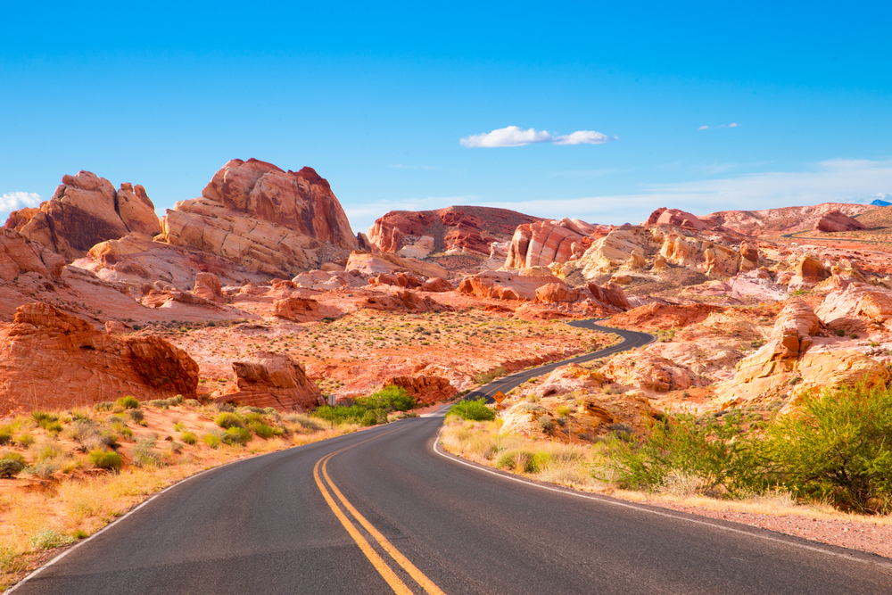 A paved road marks a path through large red rock formations in a desert landscape.