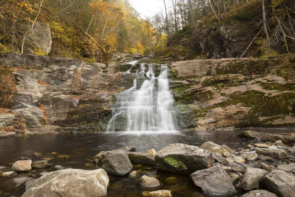 Blurred long exposure of the main waterfall at Kent Falls State Park in Kent, Connecticut, with fall foliage on the banks of Falls Brook.