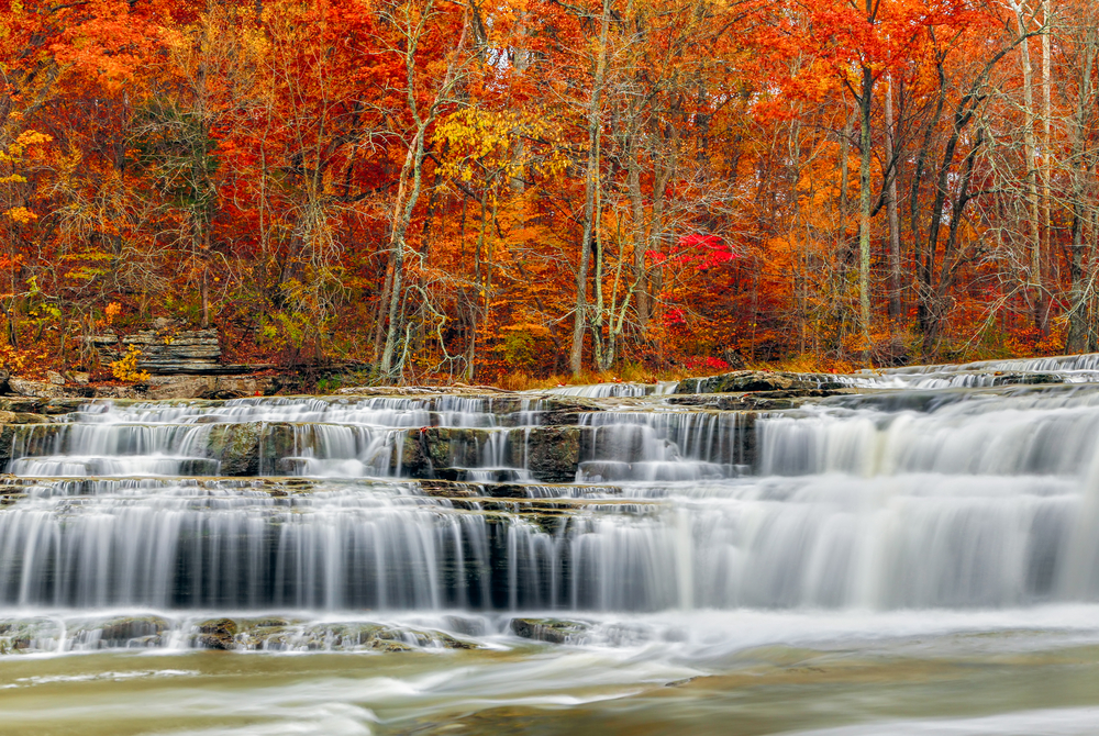 Whitewater pours over rock ledges at Indiana's Upper Cataract Falls with beautiful, colorful fall foliage.