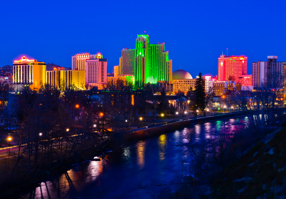 A cityscape at night. Green, red, and yellow lights shine on the buildings that stand beside a waterway.
