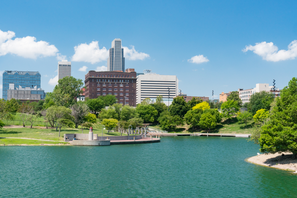 A cityscape peaks out from behind green trees across a blue lake.