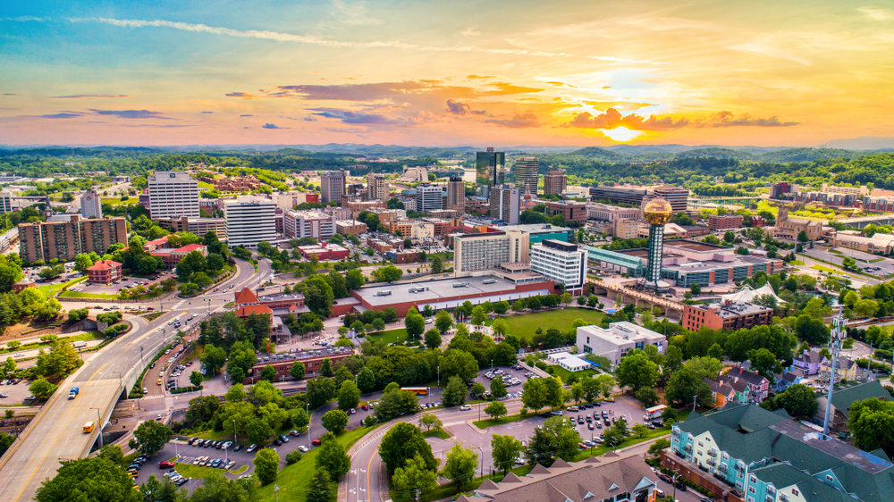 Aerial view of cityscape dotted with green trees under a setting sun.